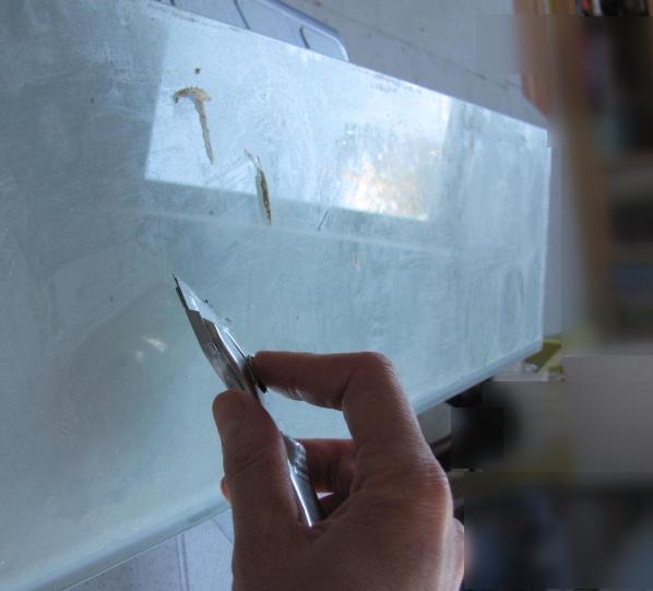 Скребком снимаем отложения со стеклянной полки